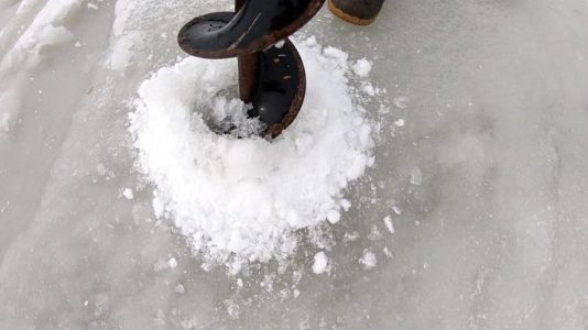 Man helps another ice fisherman who fell into lake